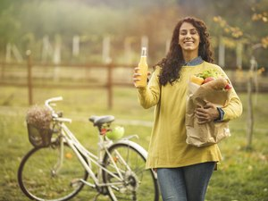 Woman drinking juice and holding shopping bag near her bicycle