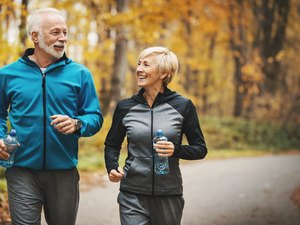 Senior couple jogging in a fores