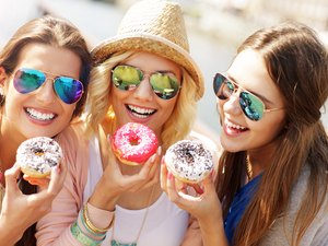 Group of friends eating donuts in the city