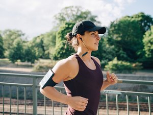woman listening to music while running on a bridge outside