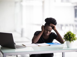 African american businesswoman or student with laptop computer and papers at office