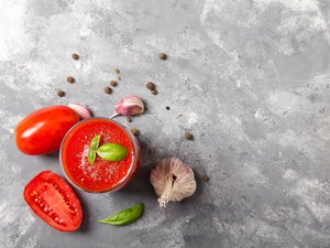 Tasty tomato juice with fresh spices, garlic, pepper and basil.