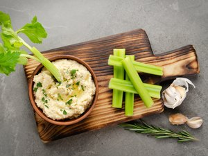 Flat lay view at vegetable Hummus dip dish topped with chickpeas and olive oil served with celery slices