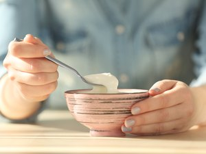 closeup of bowl with yogurt and spoon in female hands
