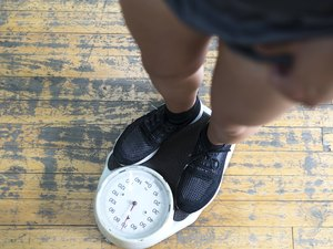 lower body of a man checking hypoglycemia's effect on weight gain or loss on a scale