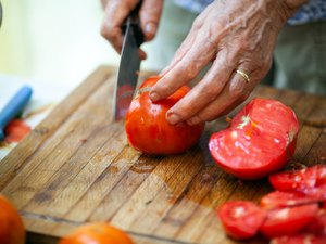 Close-up of Senior Adult Woman Slicing Tomato on Wooden Cutting Board - Stock Photo