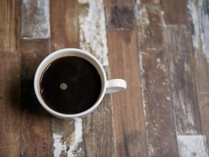 Black coffee in white cup on wooden table
