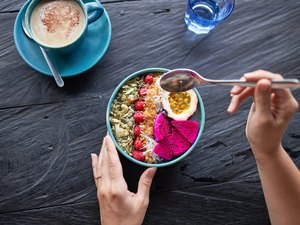 Healthy person eating delicious superfood cereal breakfast with fresh fruits and nuts with musli