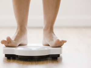 A woman's feet standing on a bathroom scale with toes lifted