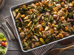 Top view of a sheet pan with slow-carb foods including chicken and vegetables