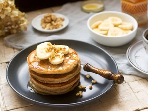 Pancakes with banana, nuts and honey, served with tea