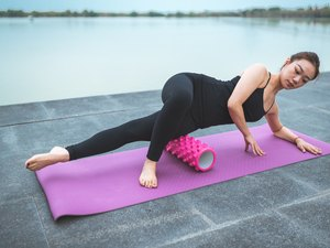 woman using a foam roller to relieve tight muscles on pink mat outside