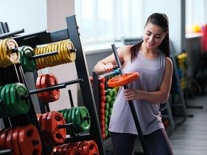 Beautiful sporty young brunette woman in sportswear in the gym.