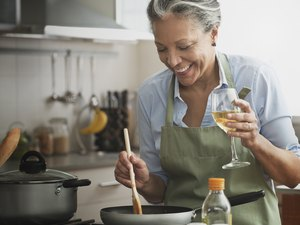 Hispanic woman cooking with wine in kitchen