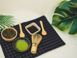 matcha green tea benefits and bamboo whisk on white background. tradition japanese tea ceremonial.