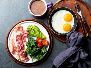 A keto diet breakfast with eggs, bacon, avocado and greens