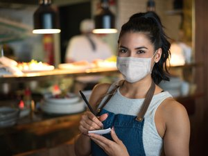 A waitress in a restaurant wearing a face mask