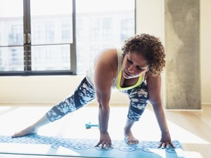 Full length of woman practicing yoga on exercise mat against window in studio