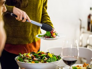 Woman serving salad while standing during party