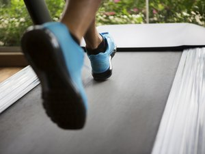Man running on treadmill wearing blue sneakers getting cardio for weight loss