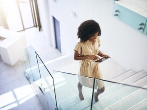 A professional woman walking up the stairs in her office building while working on a tablet