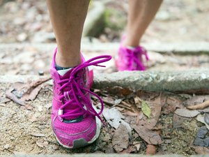 Hiking shoes on trail walking to lose weight in mountains