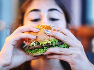 Close-Up Of Woman Eating Burger