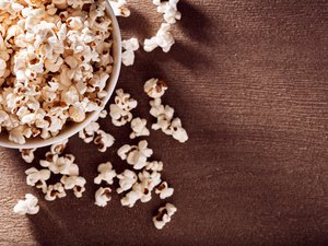 White bowl filled with popcorn spilled over the table