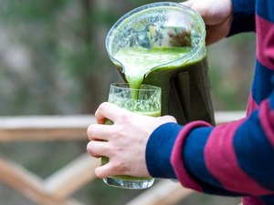 Closeup of behind, back of young man standing outside, outdoors, holding plastic blender container, pouring green vegetable, kale smoothie into drinking glass