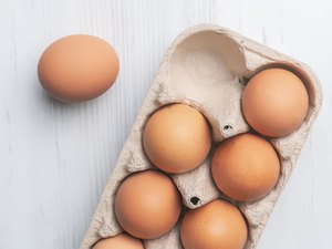 fresh eggs in paper tray on white surface b