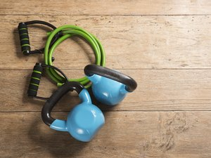 Flat Lay image of kettlebells and a resistance band on a wooden floor