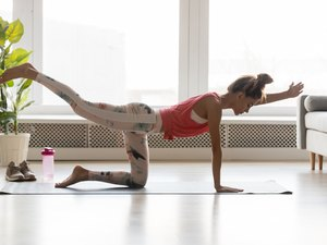 Fit woman standing in plank pose with arm leg up