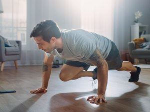 Strong Athletic Fit Man in T-shirt and Shorts is Doing Mountain Climber Exercises While Using a Stopwatch on His Phone. He is Training at Home in His Spacious Apartment with Minimalistic Interior.