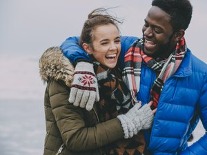 Young Couple Laughing On A Winter Beach and Being Thankful
