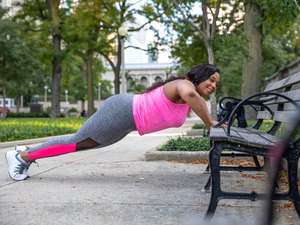 woman doing incline push-ups outdoors on a bench as part of a full-body workout