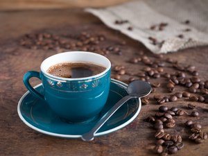 Coffee cup and roasted beans on a wooden background