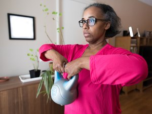 Woman strength training at home with kettlebell