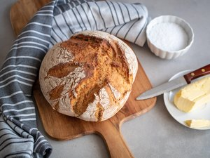 Loaf bread on a chopping board with butter
