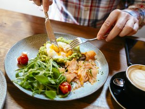 Man eating avocado toast with egg, salmon and arugula salad to lose weight in two weeks