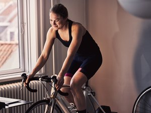 Woman cycling indoors using a trainer and her bike to get health benefits