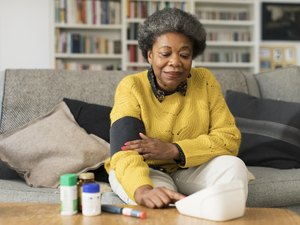 Woman sitting on a couch wearing blood pressure cuff with medications