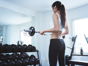 Asian women at gym she Weightlifting to strengthen muscles