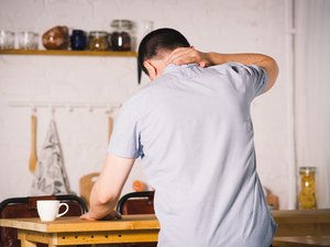 Neck pain, man suffering from upper back pain