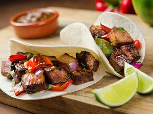 Beef fajitas with sauce and lime on the side