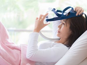 Woman lay in bed wearing CPAP mask ,sleep apnea therapy