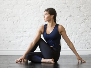 Young attractive woman in Ardha Matsyendrasana pose, studio background