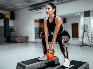 Muscular woman doing gym workout at gym.