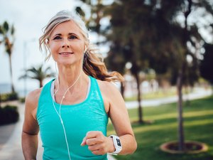 An active mature woman running in the park