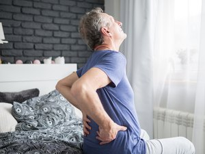 Senior man lower back pain on the left side siting on bed