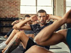 Fitness people in a row doing sit ups